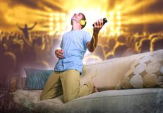 Young happy and excited man jumping on sofa couch listening to m. Usic with mobile phone and headphones playing air guitar crazy having fun at home living room stock photos