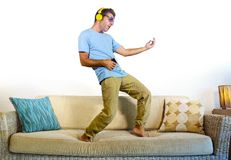 Young happy and excited man jumping on sofa couch listening to music with mobile phone and headphones playing air guitar crazy hav Royalty Free Stock Image