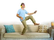 Young happy and excited man jumping on sofa couch listening to music with mobile phone and headphones playing air guitar crazy hav. Ing fun at home living room Stock Photos