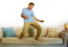 Young happy and excited man jumping on sofa couch listening to music with mobile phone and headphones singing and dancing crazy ha. Ving fun at home living room Stock Images