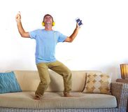 Young happy and excited man jumping on sofa couch listening to music with mobile phone and headphones singing and dancing crazy ha. Ving fun at home living room Stock Image