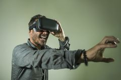 Young happy and excited man wearing virtual reality VR goggles headset experimenting 3d illusion playing video game touching. Illusion environment surprised  on royalty free stock images