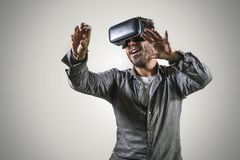Young happy and excited man wearing virtual reality VR goggles headset experimenting 3d illusion playing video game touching. Illusion environment surprised  on royalty free stock photo