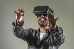 Young happy and excited man wearing virtual reality VR goggles headset experimenting 3d illusion playing video game touching. Illusion environment surprised  on stock images