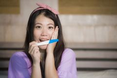 Young happy excited pregnant Asian Korean woman at home holding predictor and checking positive result on pregnancy test feeling b stock image