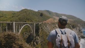 Young happy excited tourist man with backpack watching epic beautiful scenery of Bixby Canyon bridge, walking away. Successful middle aged male traveler stock video footage