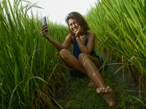 Young happy and exotic islander Asian girl from Indonesia taking selfie self portrait photo with mobile phone smiling cheerful and. Excited posing rice field stock photography