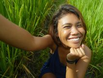 Young happy and exotic islander Asian girl from Indonesia taking selfie self portrait photo with mobile phone smiling cheerful and. Excited posing rice field stock photos