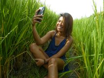 Young happy and exotic islander Asian girl from Indonesia taking selfie self portrait photo with mobile phone smiling cheerful and. Excited posing rice field royalty free stock photo