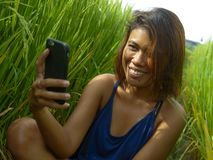Young happy and exotic islander Asian girl from Indonesia taking selfie self portrait photo with mobile phone smiling cheerful and. Excited posing rice field royalty free stock photography
