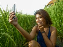 Young happy and exotic islander Asian girl from Indonesia taking selfie self portrait photo with mobile phone smiling cheerful and. Excited posing rice field stock photo