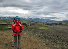 Young and happy experienced hiker girl with heavy backpack enjoying the view on Laugavegur hiking trail from Thorsmork to royalty free stock photography