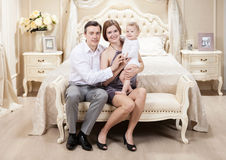 Young happy family with a baby on bed Stock Photo