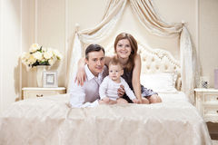 Young happy family with a baby on bed Royalty Free Stock Photos