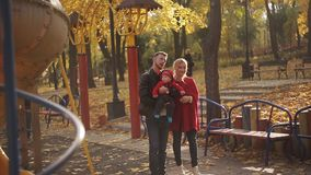Young and happy family with a baby in the playground. swings and carousels in the park stock footage