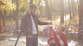 Young mom and dad with an infant playing on the playground. swings and carousels in the park for children stock video