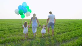 Young happy family with balloon goes on a green field with two children. Family with childs, kids walking on summer stock footage