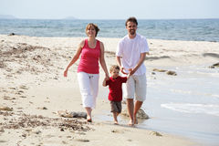 Young happy family on the beach. Young happy family taking a walk along the beach Stock Photo
