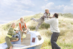 Young happy family at beach with boat Royalty Free Stock Photography