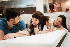 Young happy family checks on softness of orthopedic mattress, lying on bed in furniture store. stock images