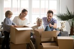 Young happy family with children packing boxes on moving day. Young happy family with kids packing boxes on moving day together sitting on sofa in modern living royalty free stock images