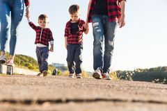 Young happy family with childrens having fun in nature. Parents walk with children in the park stock images
