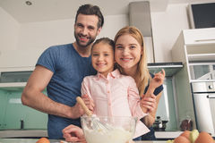 Young happy family cooking dough together mixing stock photography