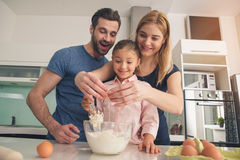 Young happy family cooking dough together mixing. Young family cooking dough together smiling in kitchen Royalty Free Stock Image