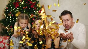 Young happy family of four sitting by the Christmas tree and blowing golden confetti. Cute mother, father and two. Daughters celebrating Christmas together stock footage