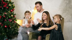 Young happy family of four sitting by the Christmas tree and holding sparklers. Cute mother, father and two daughters. Celebrating Christmas together stock video