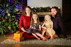 Young happy family of four sitting by a fireplace on Christmas eve Stock Photos