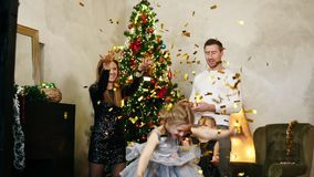 Young happy family of four standing by the Christmas tree and throwing up golden confetti. Cute mother, father and two. Daughters celebrating Christmas together stock footage