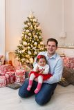 Young happy family in front of a Christmas tree Royalty Free Stock Image