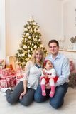 Young happy family in front of a Christmas tree Stock Photo