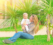 Young happy family having fun. On backyard, mother with little daughter sitting on green grass and enjoying nice sunny day, love concept Stock Images