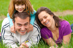 Young happy family having fun in the grass Royalty Free Stock Photo