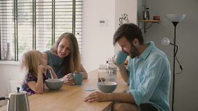 Young happy family is having peaceful breakfast in the morning. Slow motion, Steadicam shot stock footage