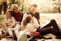 Happy family having picnic. Father teaching daughter to read. royalty free stock photography