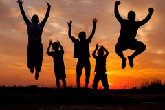 Young happy family jumping silhouettes  at sunset Royalty Free Stock Photo