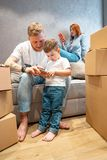 Young happy family with kid unpacking boxes together sitting on sofa stock photography