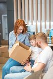 Young happy family with kid unpacking boxes together sitting on sofa stock image