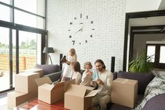 Young happy family with kids unpacking boxes in living room Stock Images