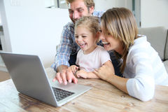 Young happy family on laptop at home Stock Photo