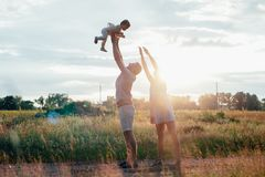 Young happy family with little beautiful baby with blue eyes walking in summer park at sunset. Royalty Free Stock Photos