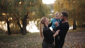 Happy family in autumn Park near the lake walk with a young son. stock footage
