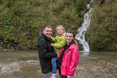 Young happy family: mom, dad and daughter on the background of a mountain waterfall royalty free stock photos