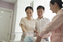 Young happy family with nurse looking down at their newborn in the hospital nursery Stock Photos