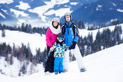 Young happy family with one child, skiing in the mountains Royalty Free Stock Photography