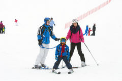Young happy family with one child, skiing in the mountains royalty free stock photos