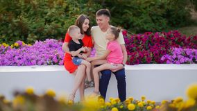 Young happy family in the Park among the flowers. The little son sits on his mother`s lap, the daughter sits on his. Father`s lap. Close up stock image